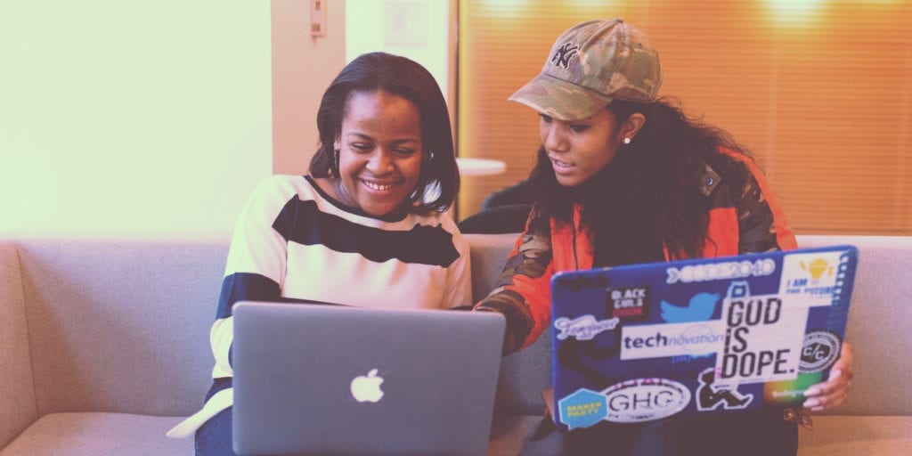 Image of two female-presenting Black individuals sitting next to each other, with one pointing to the other's laptop screen. The other person is smiling.